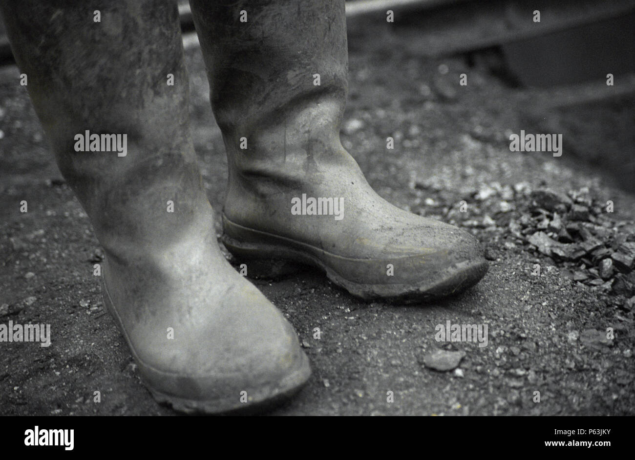 Rubber boots on coal mine. China is one of the largest producer of coal in the world and it has also one of the worse recorded mining conditions. And  Stock Photo