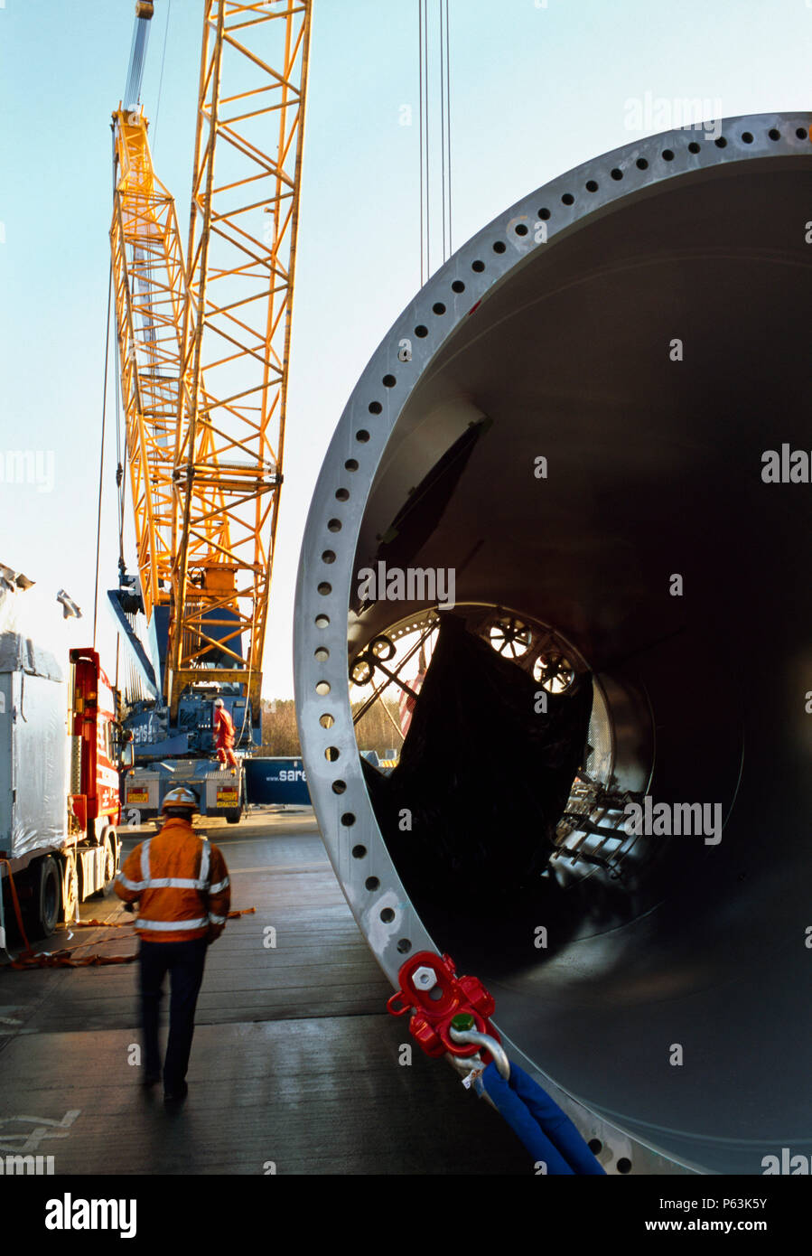 Workers unload huge sections of tubing that forms the body of a giant Enercon wind turbine. Worksop United Kingdom. December 2008. Stock Photo