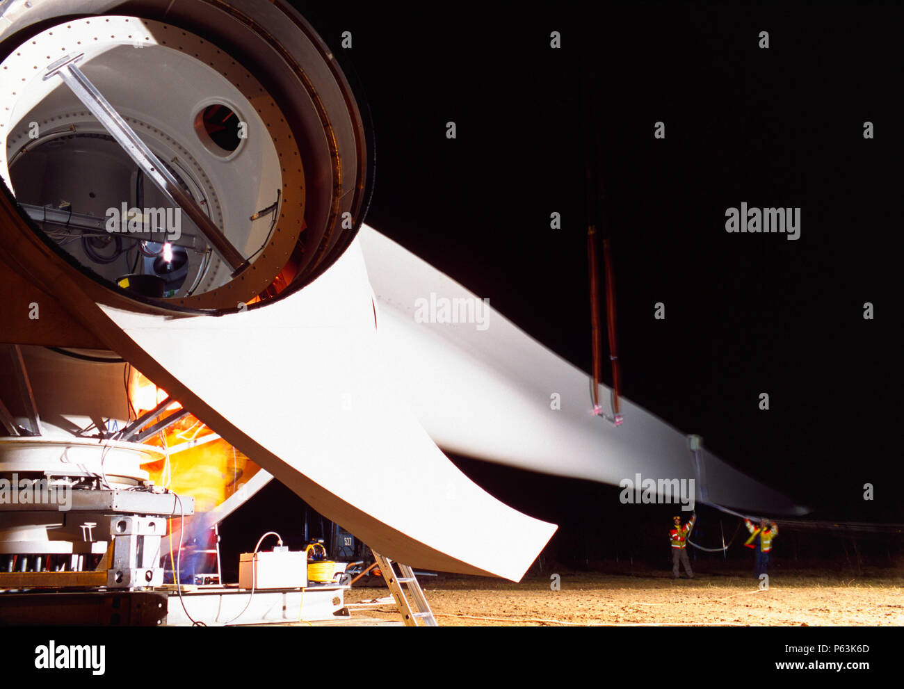 Long exposure image of workers assembling the hub and blades of a giant Enercon wind turbine at night. Stock Photo