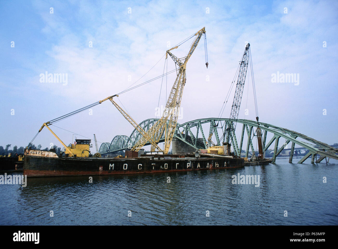 A floating crane is used to lift damaged sections of the rail bridge into central Belgrade, Serbia, damaged by NATO bombardment in 1998 - Stock Image