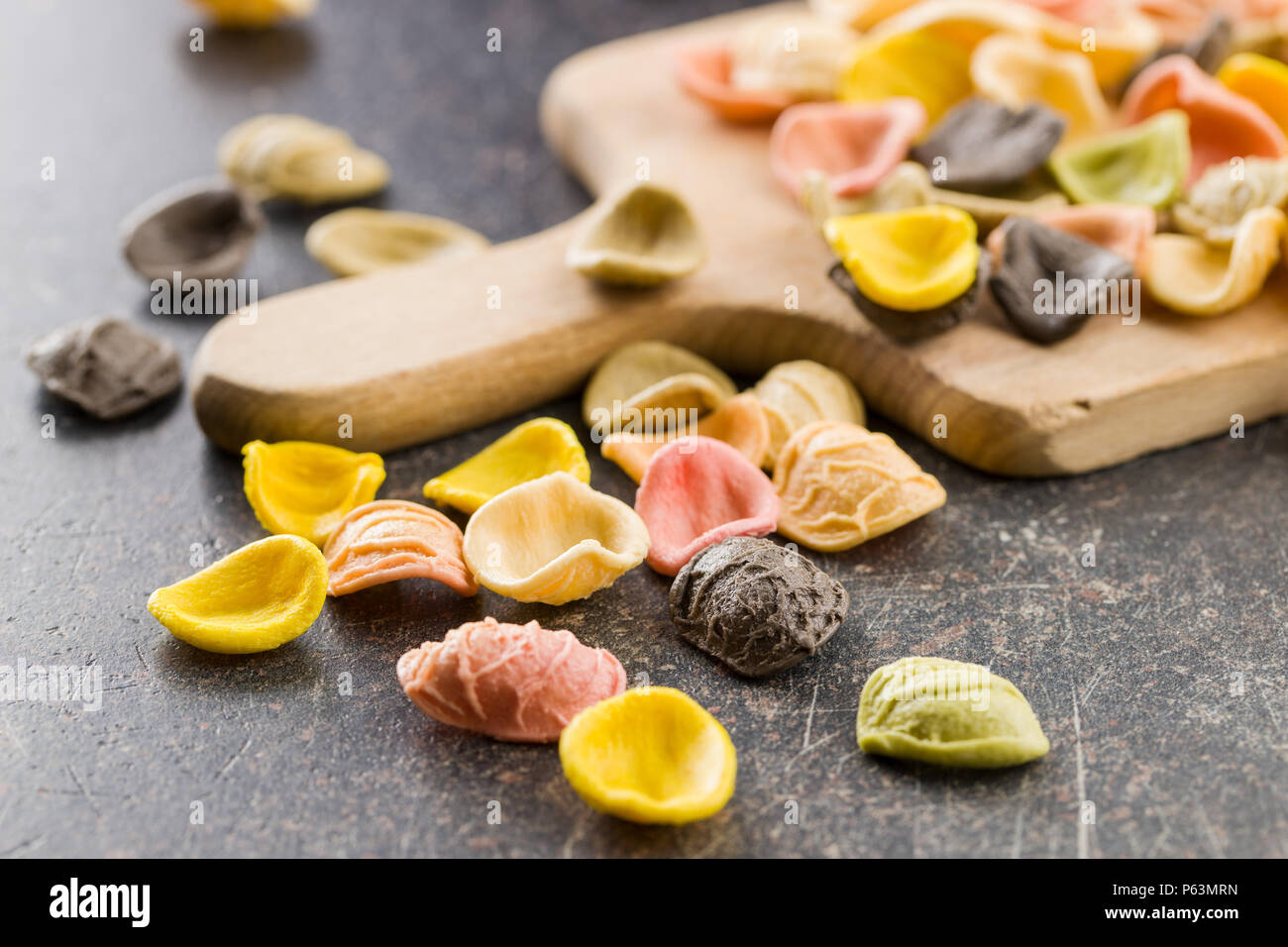 Italian rainbow pasta on old kitchen table. - Stock Image