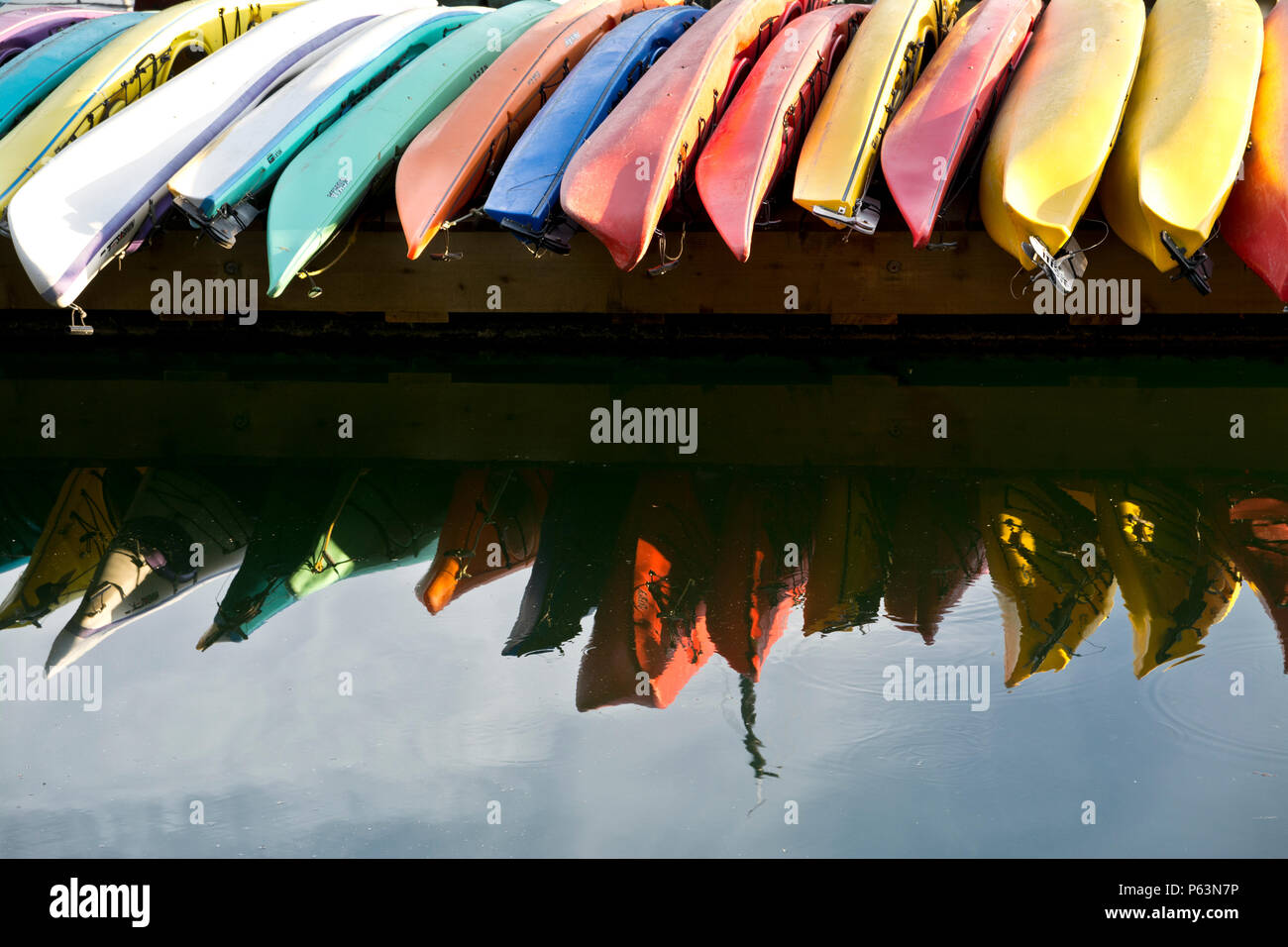 Colourful kayaks lined up on the dock in Montague Harbour marina on Galiano Island,British Columbia, Canada. - Stock Image