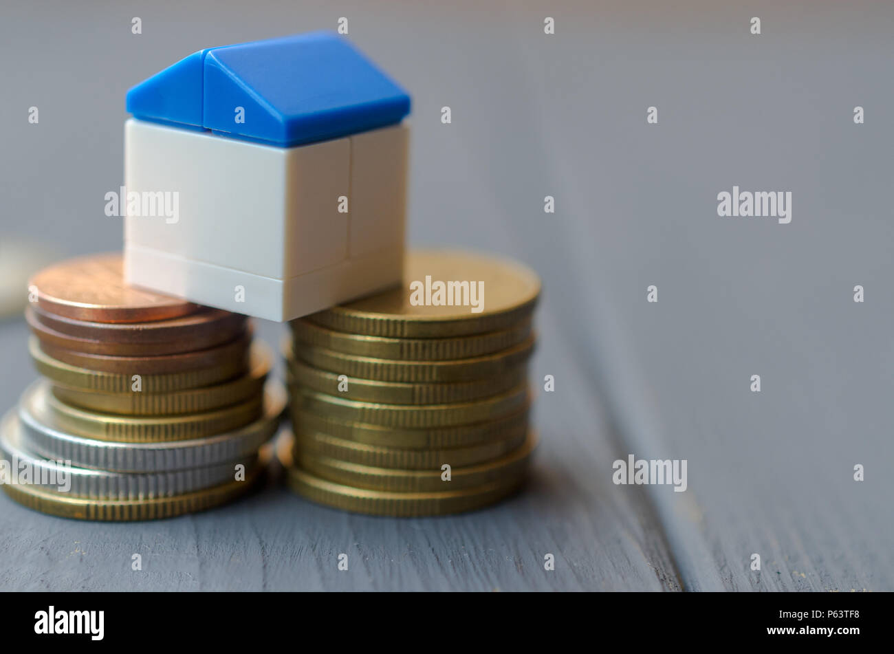 The concept of loans for housing. White house with a blue roof on a pile of coins Stock Photo
