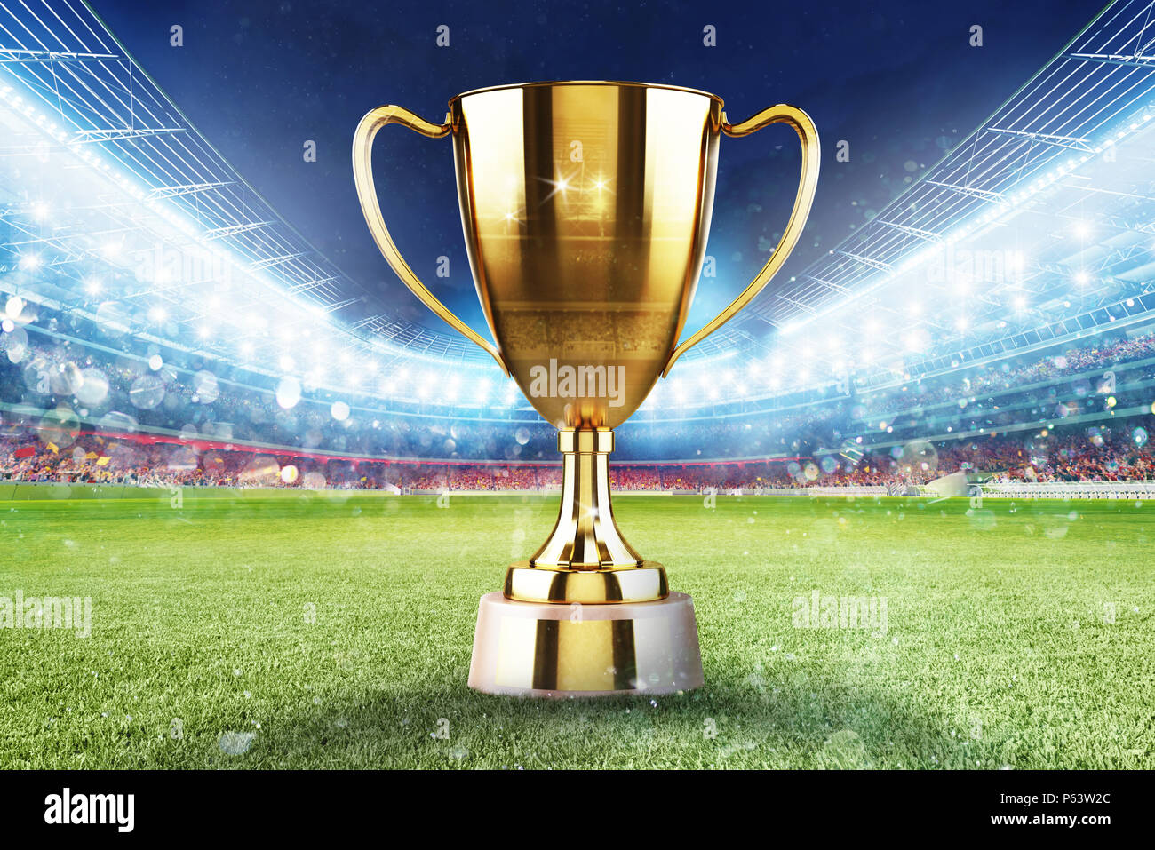 Golden winner s cup in the middle of a soccer stadium with audience - Stock Image