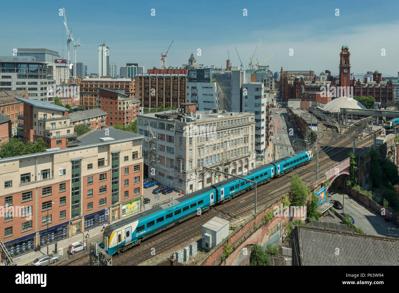 An Arriva Train arrives at Oxford Road station in Manchester, with the city's skyline in the background. - Stock Image