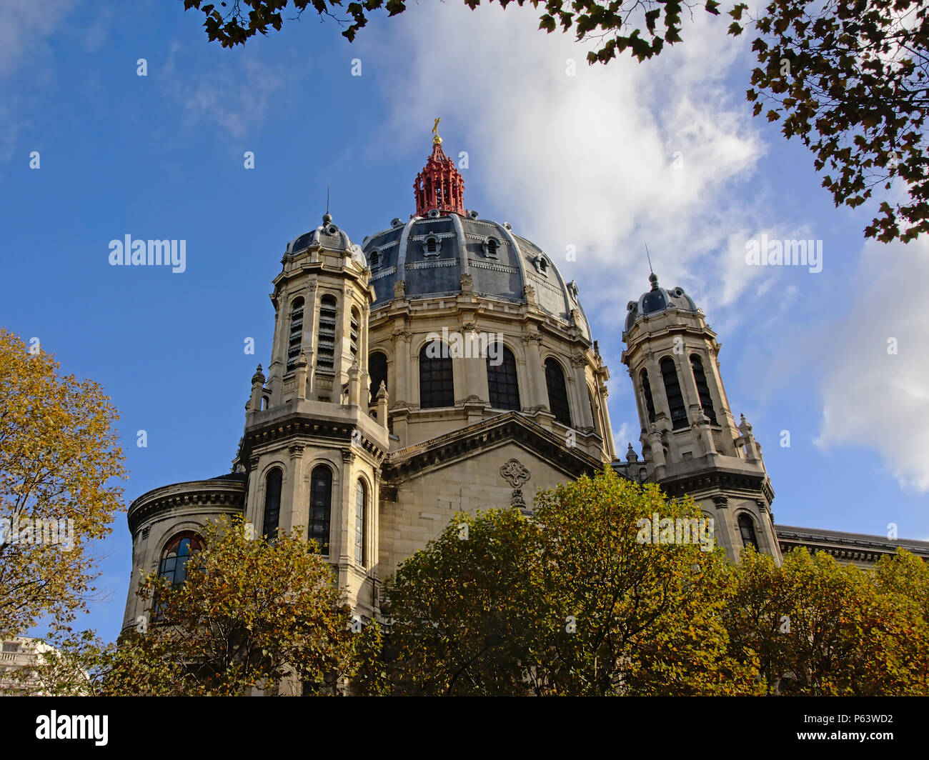 Cupola with red crown and towers of the Saint Augustin church in Second Empire style in Paris, France on a sunny day with blue sky and soft clouds, lo - Stock Image