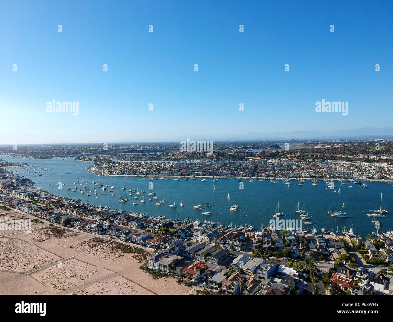 An aerial shot at 330 feet/100 meters looking out over the Newport skyline, the Balboa Peninsula and the Newport Bay full of boats. Captured in Southe - Stock Image