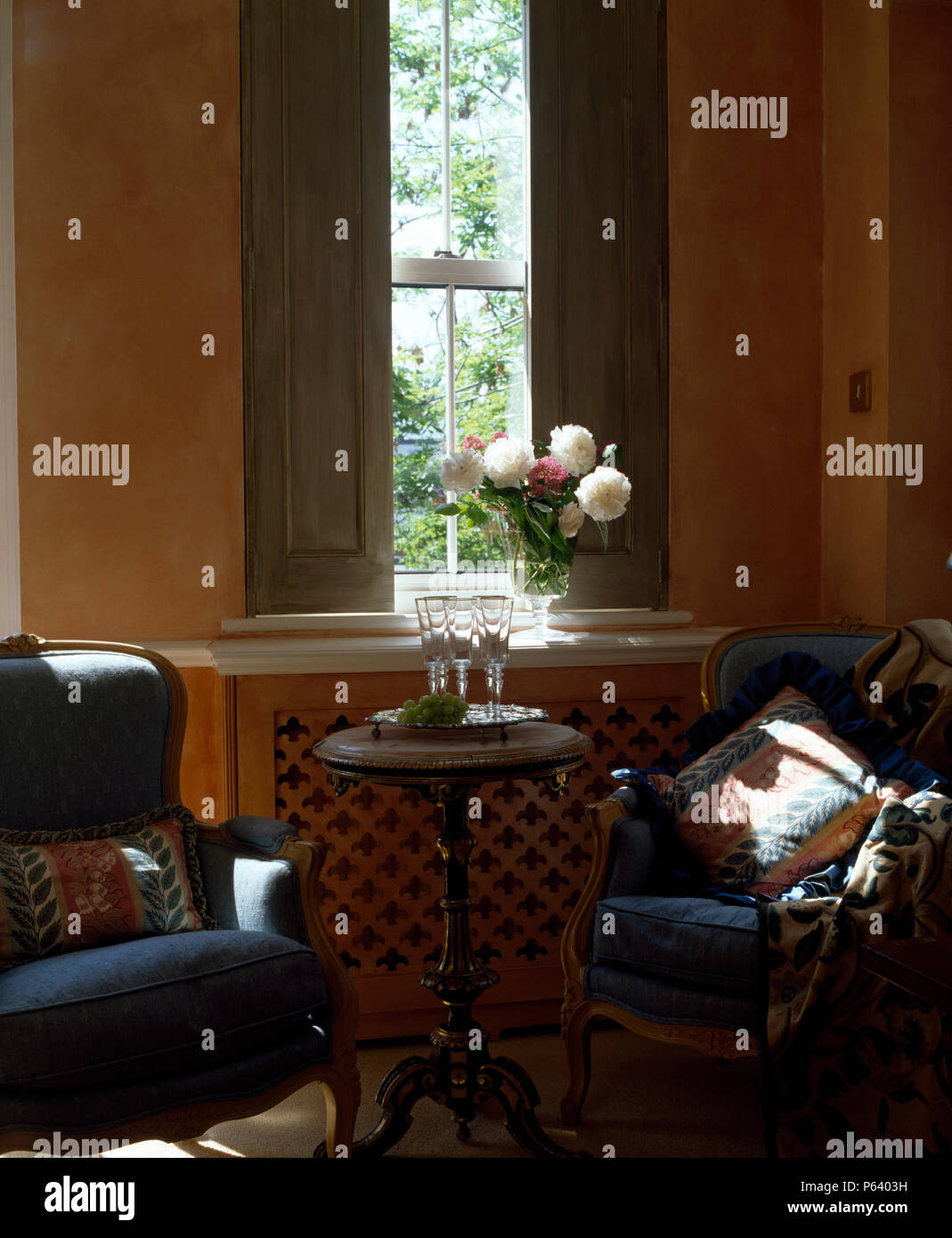 Blue Armchairs And Small Antique Table In Front Of Windows