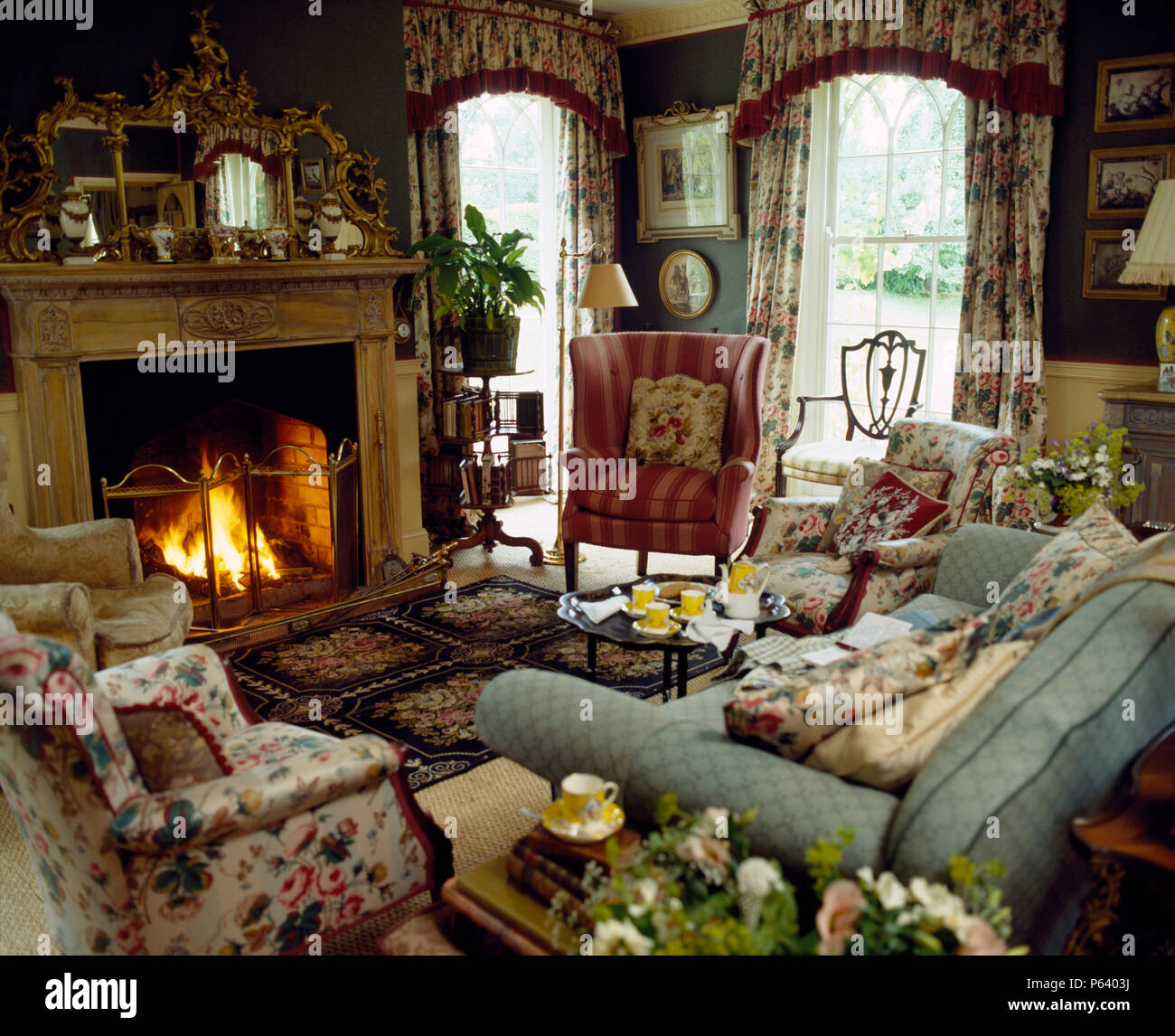 Pale Blue Sofa And Pink Wing Chair In Country Sitting Room With Floral Armchairs Arranged Around Fireplace With Lighted Fire Stock Photo Alamy