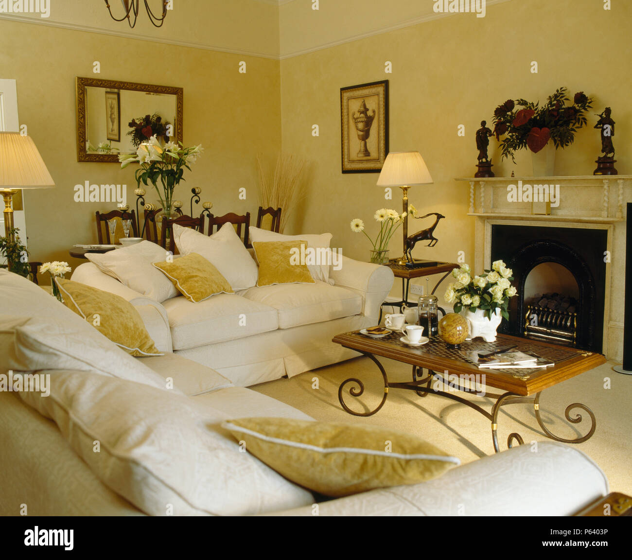 White sofas with wood metal coffee table beside the fireplace in traditional tonhouse sitting room