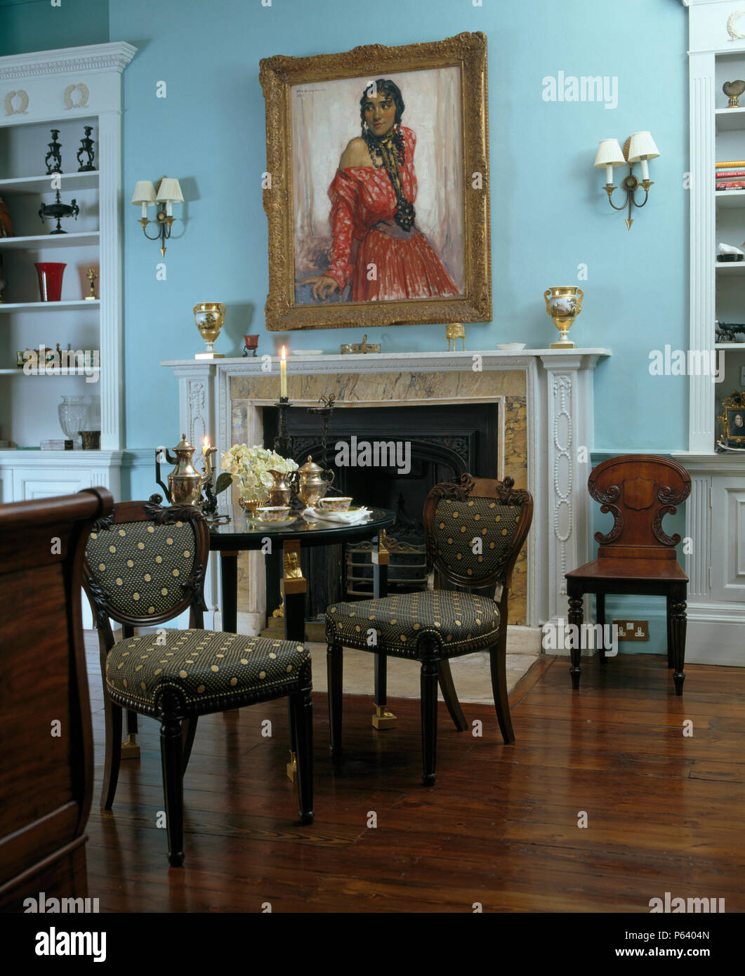 Antique upholstered chairs at small table set for breakfast ...