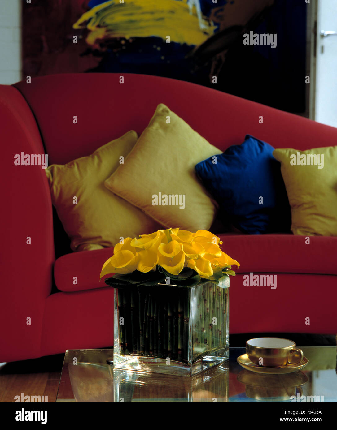 Vase of yellow calla lilies inon table in front of red sofa ...