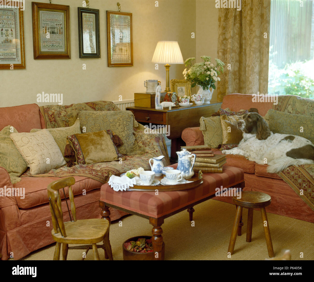Comfortable living room with tea set on upholstered stool in ...