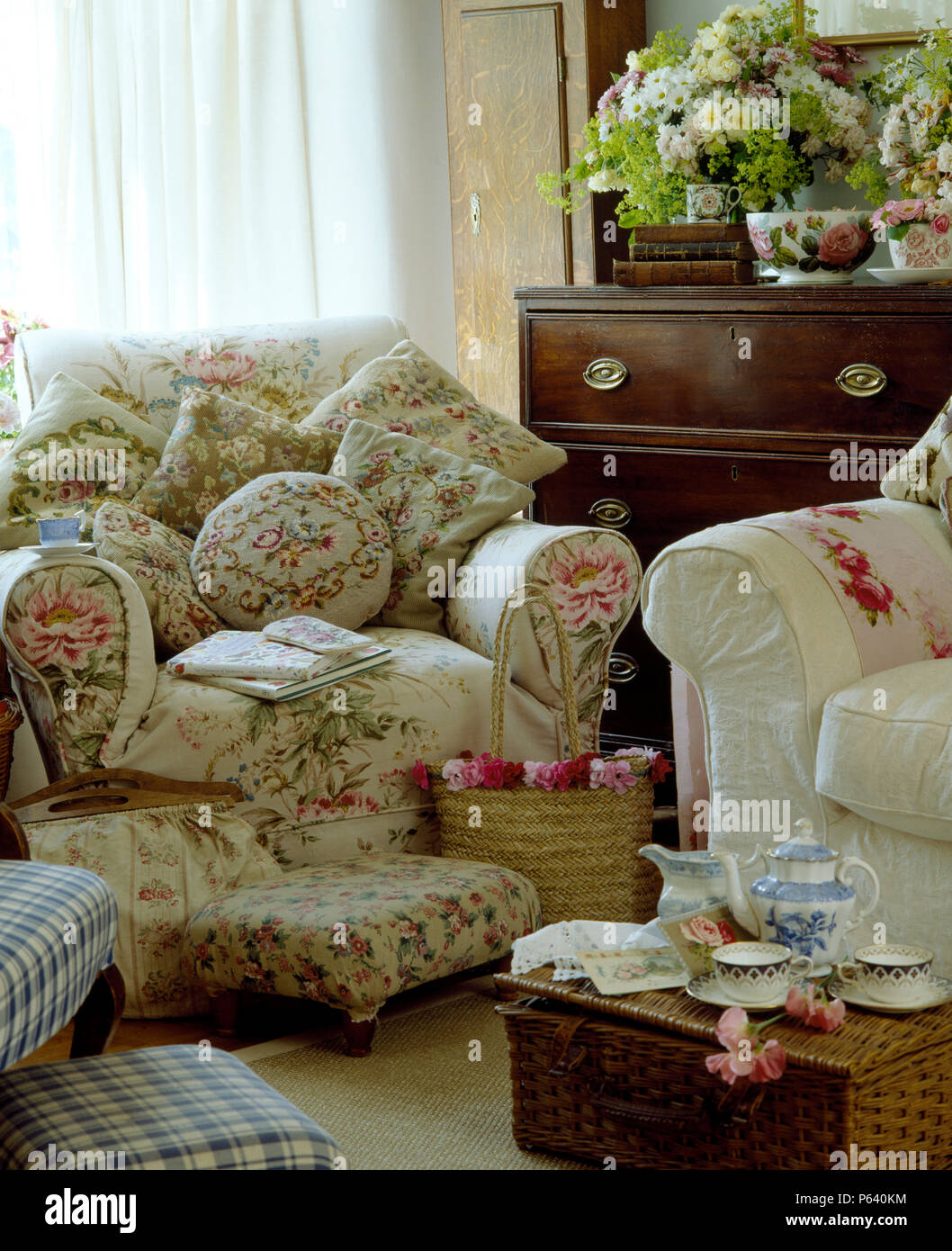 Floral armchair piled with cushions in cluttered cottage living room with tea set on wicker chest - Stock Image