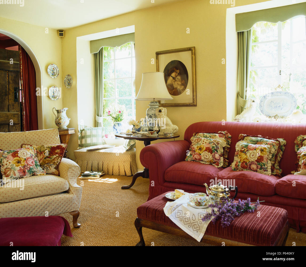 rose-patterned cushions on red sofa and cream armchair in ...