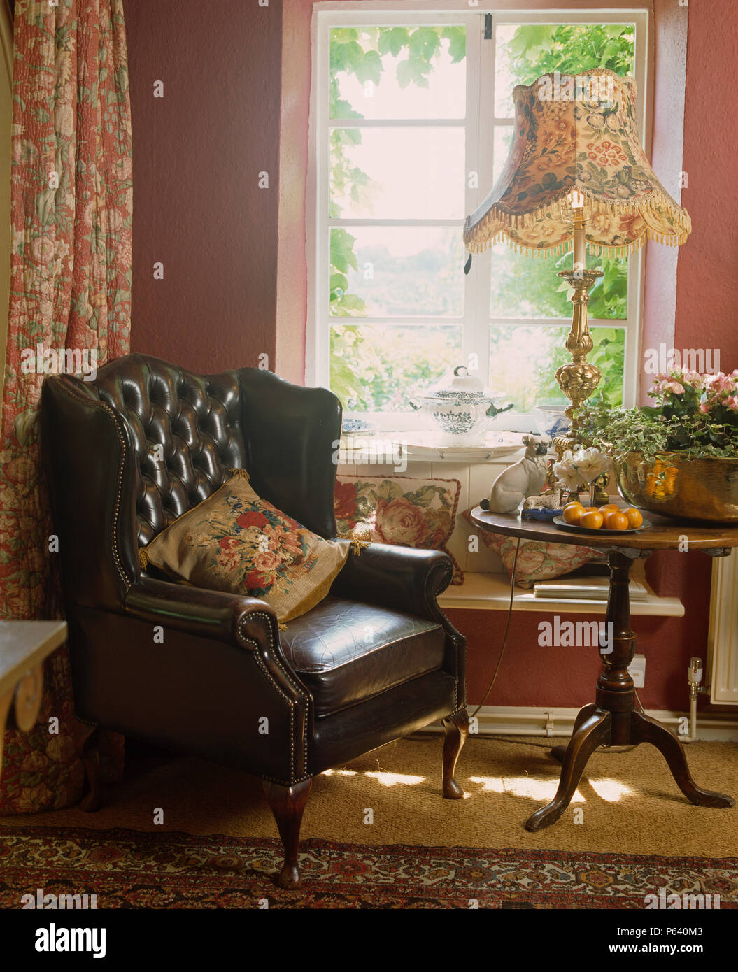 Leather wing-chair and small antique table with tall lamp in ...