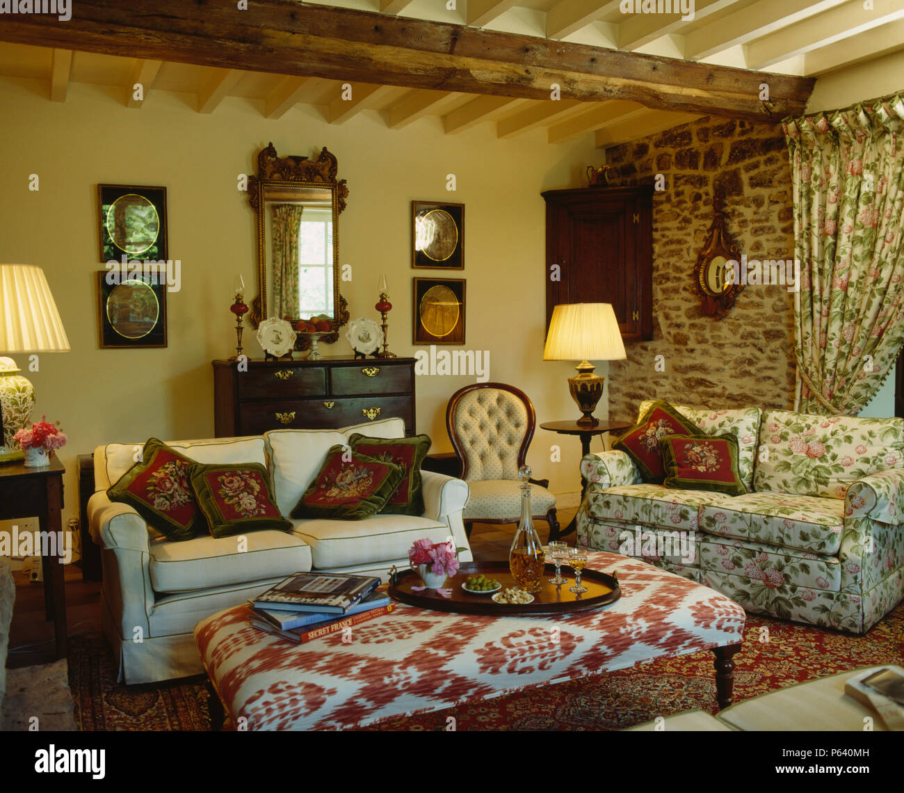 Upholstered stool and comfy sofas in fRENCH cottage living room with ...