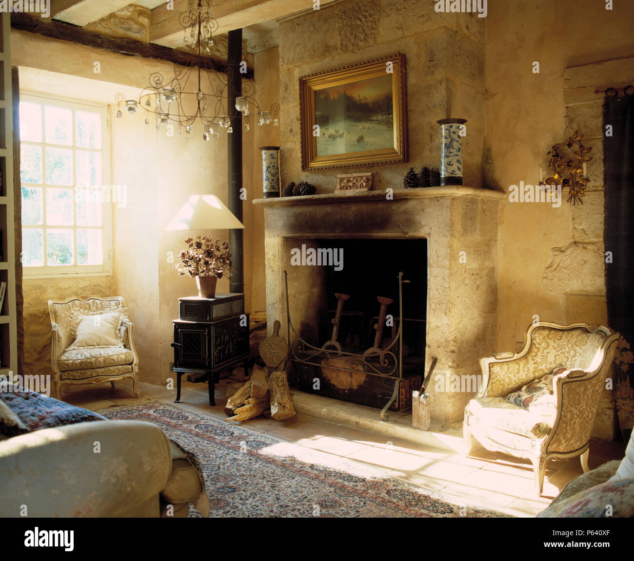 Picture above large stone fireplace in French country living room with table lamp on old cast iron stove - Stock Image