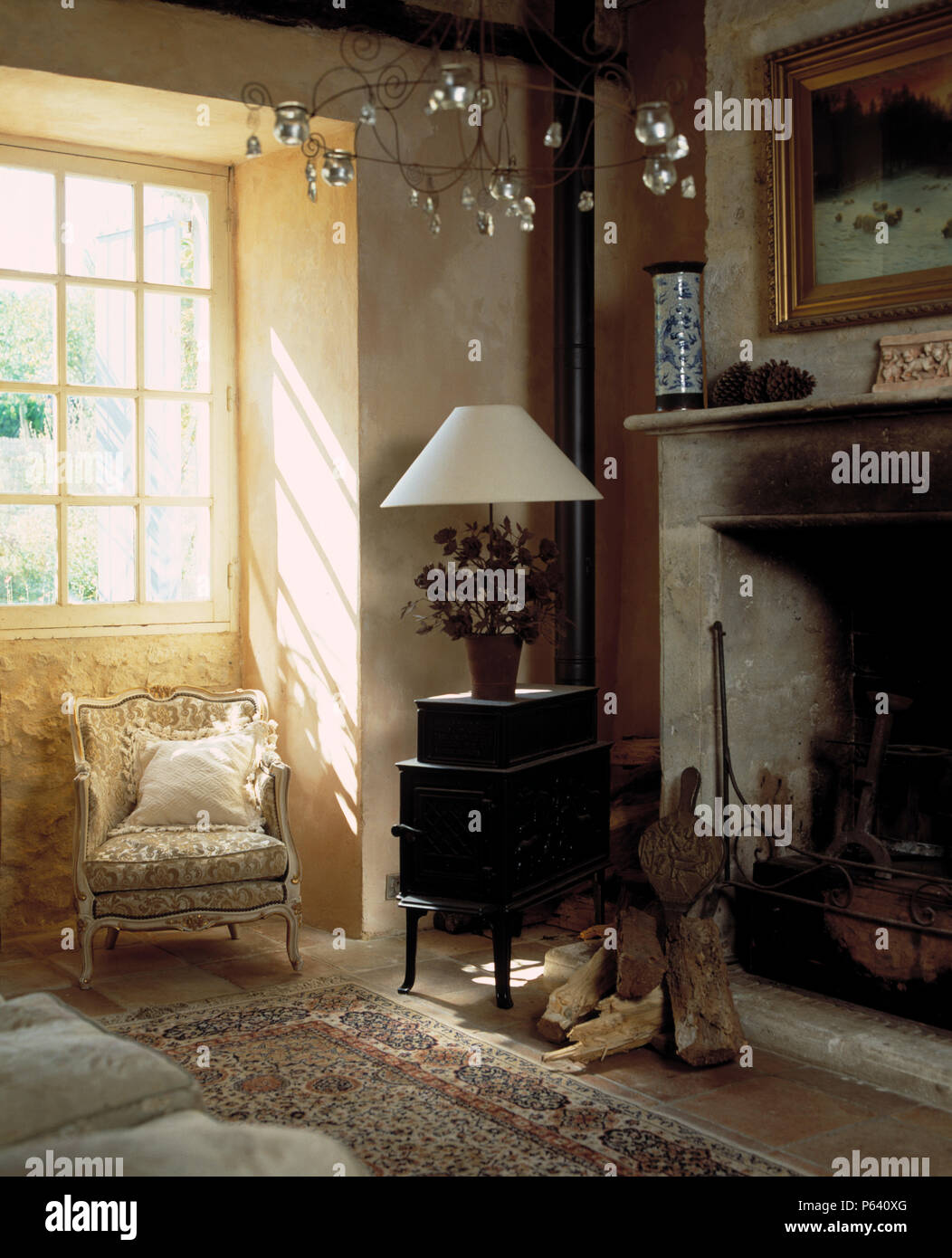 White Table Lamp On Old Cast Iron Stove Beside Stone Fireplace In