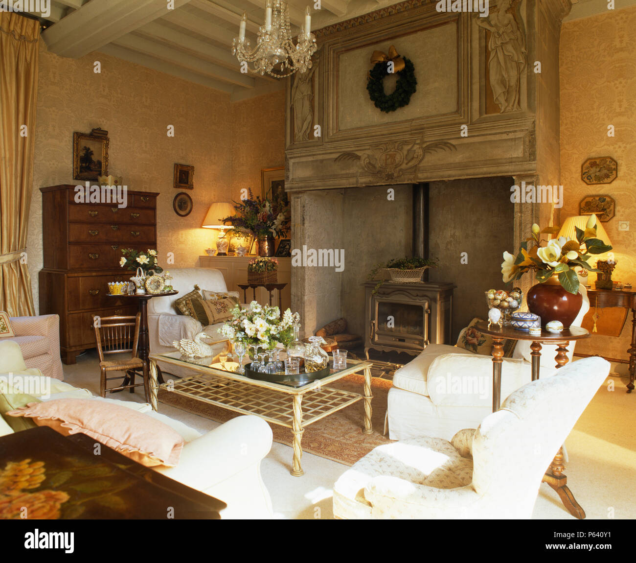 Ornate carved wood fireplace with wood-burning stove in French country sitting room with white sofas and antique furniture - Stock Image