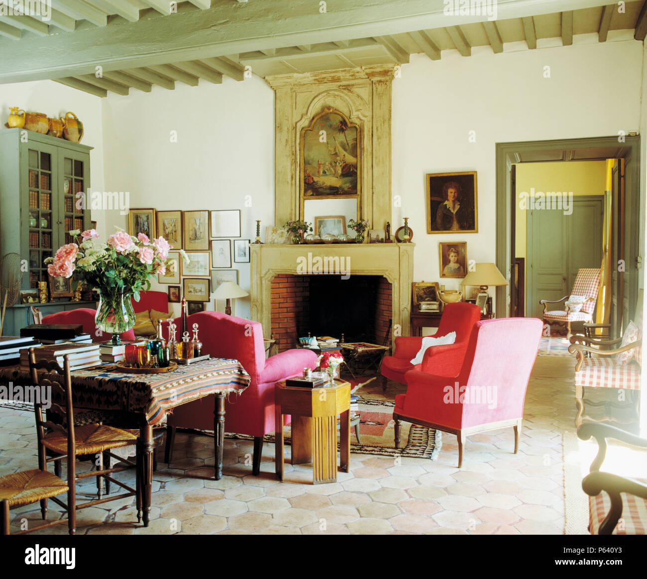 Red armchairs set around fireplace with pictorial overmantel ...