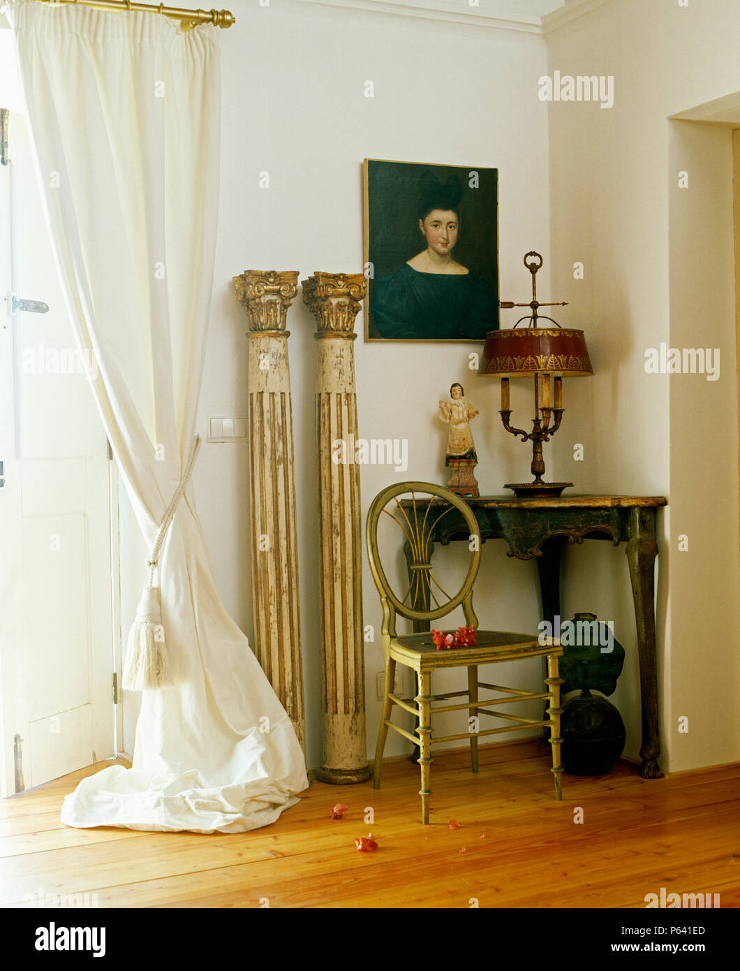Pair of neo-classical columns beside antique chair and corner table in Portuguese hall with white curtain on French windows - Stock Image