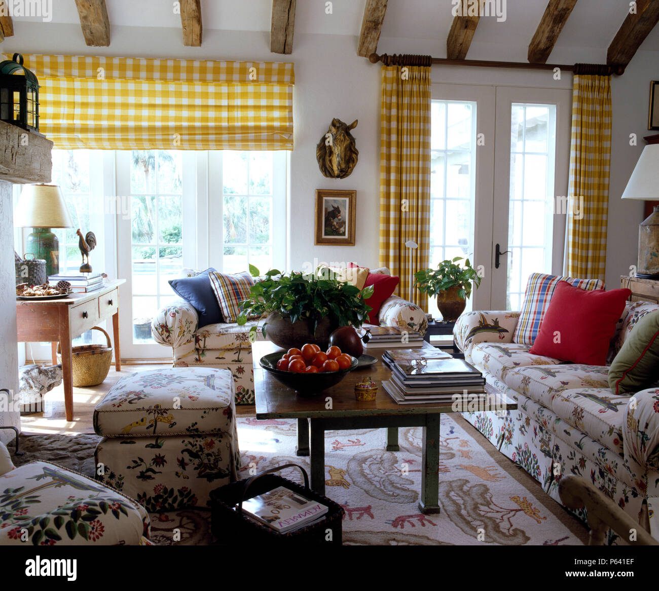 Yellow checked blind and curtains on French windows in a ...