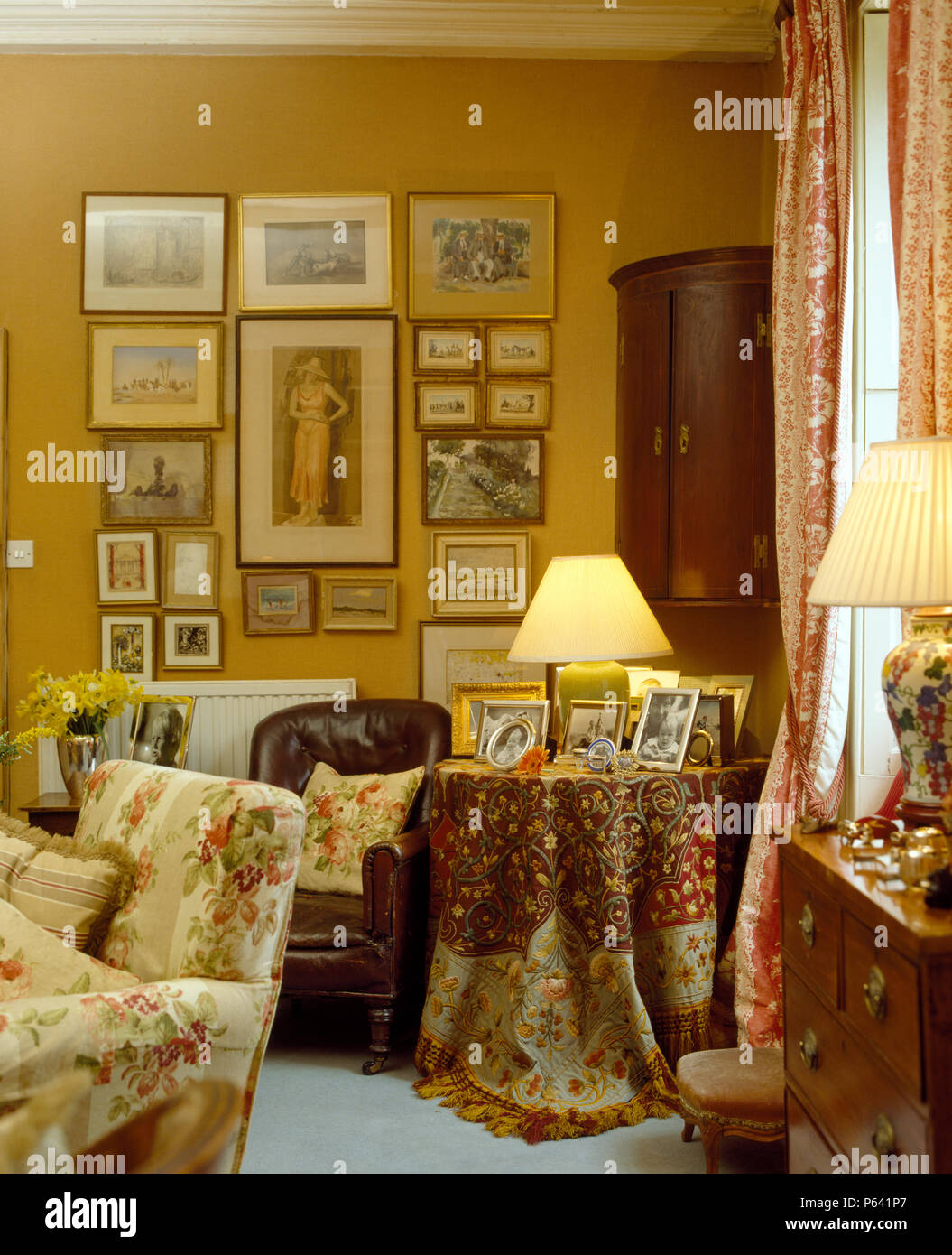 Collection of pictures on wall in corner of living room with lighted ...