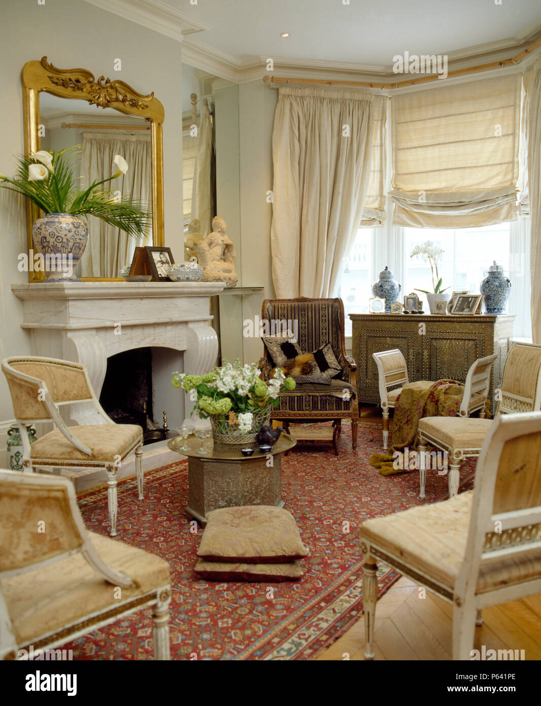 Antique gilt mirror above fireplace in elegant pale grey living room ...