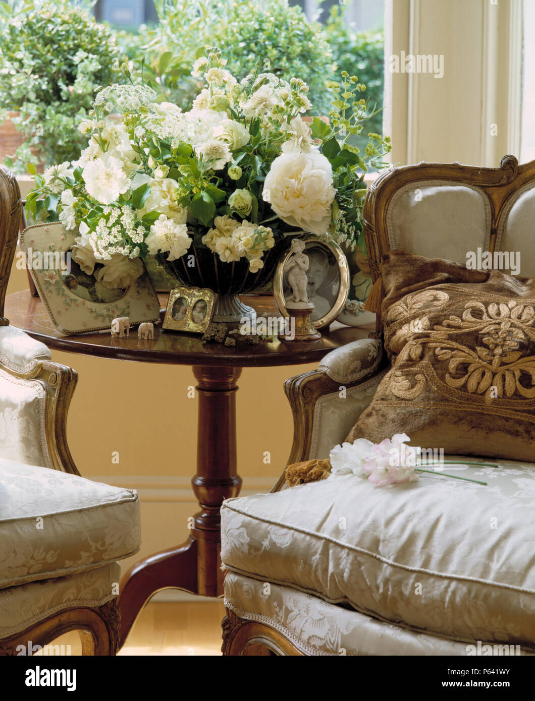 White Roses In Floral Arrangement On Antique Able In Front Of Window In  Traditional Living Room
