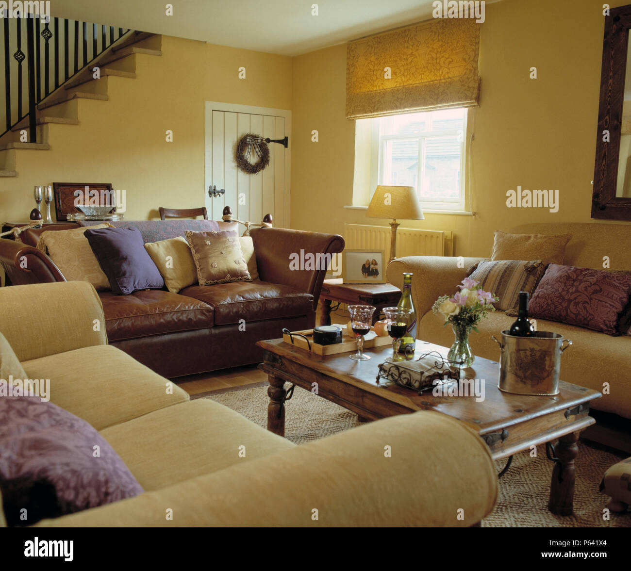 Brown Leather Sofa With Two Cream Sofas In Pale Yellow Country Sitting Room  With An Indonesian