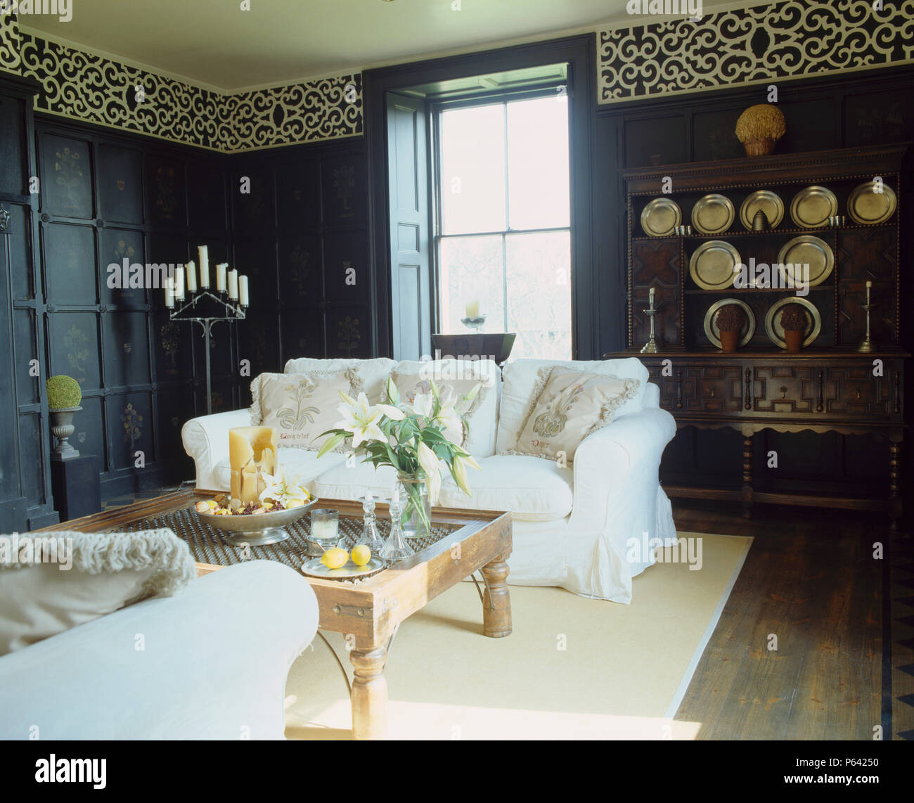 White Sofas And Cream Rug In Black Panelled Living Room With