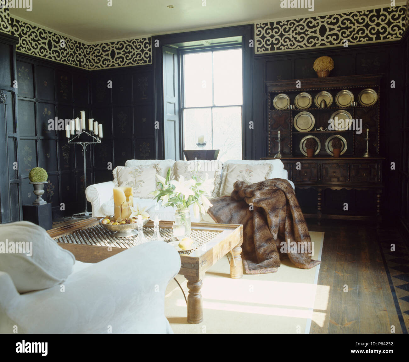 Faux Fur Throw On White Sofa In Black Panelled Living Room ...