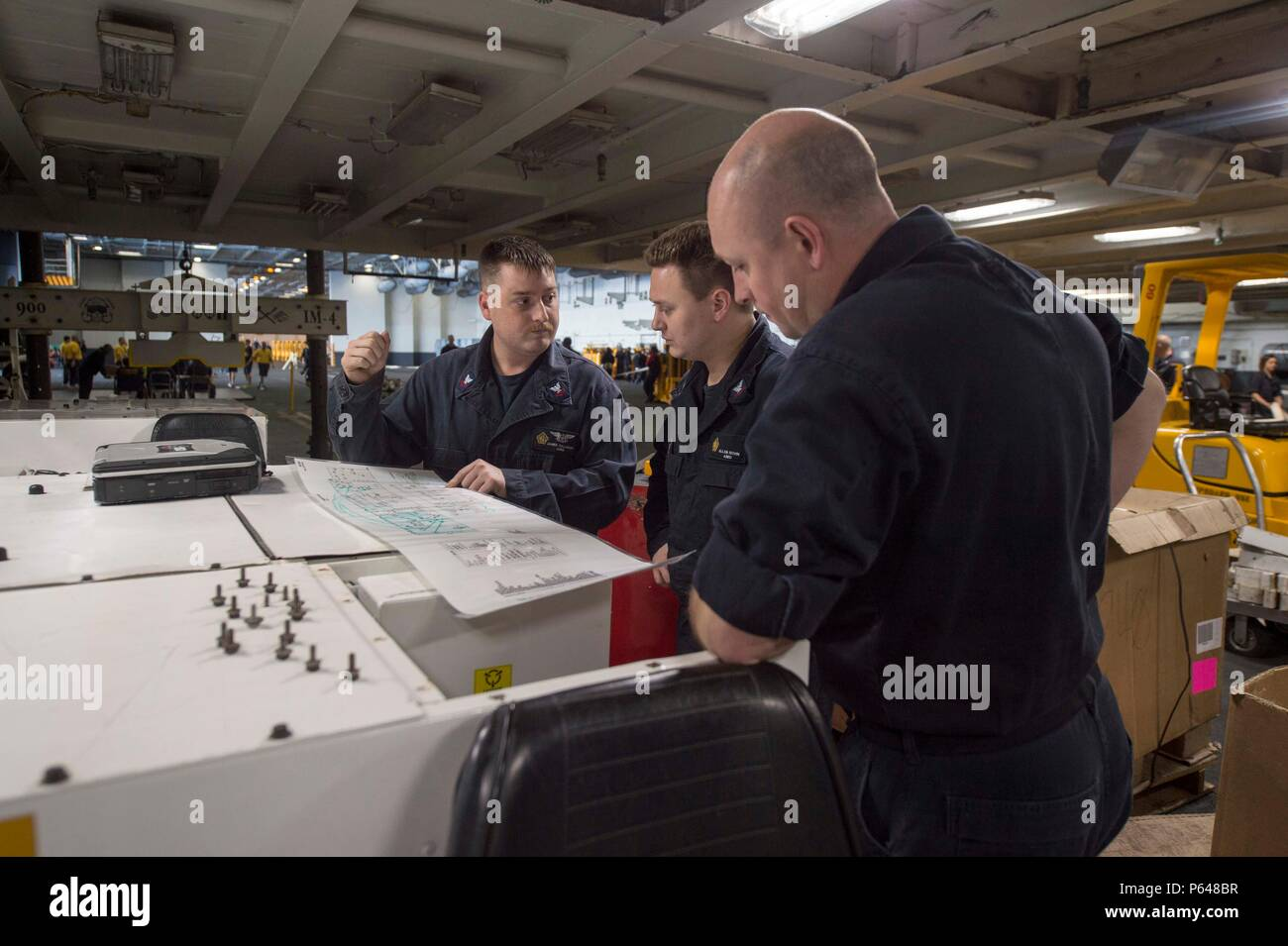 160420-N-BH414-005    ATLANTIC OCEAN (April 20, 2016) - Sailors study schematics in the hangar bay of the aircraft carrier USS Dwight D. Eisenhower (CVN 69), the flagship of the Eisenhower Carrier Strike Group. Ike is underway preparing for an upcoming scheduled deployment. (U.S. Navy photo by Mass Communication Specialist Seaman Casey S. Trietsch/Released) - Stock Image
