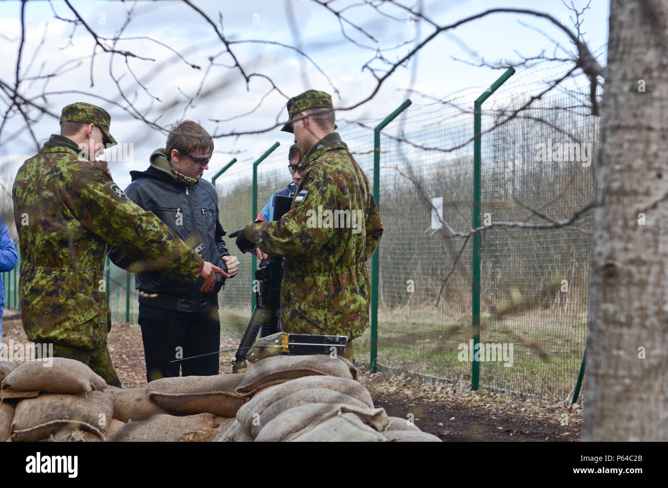 Estonian Army Soldiers help school-aged children load their weapons with plastic pellets for the lane patrol exercise during an open house at Tapa Training Base, Estonia, April 23, 2016. (U.S. Army Photo by Staff Sgt. Steven M. Colvin) - Stock Image