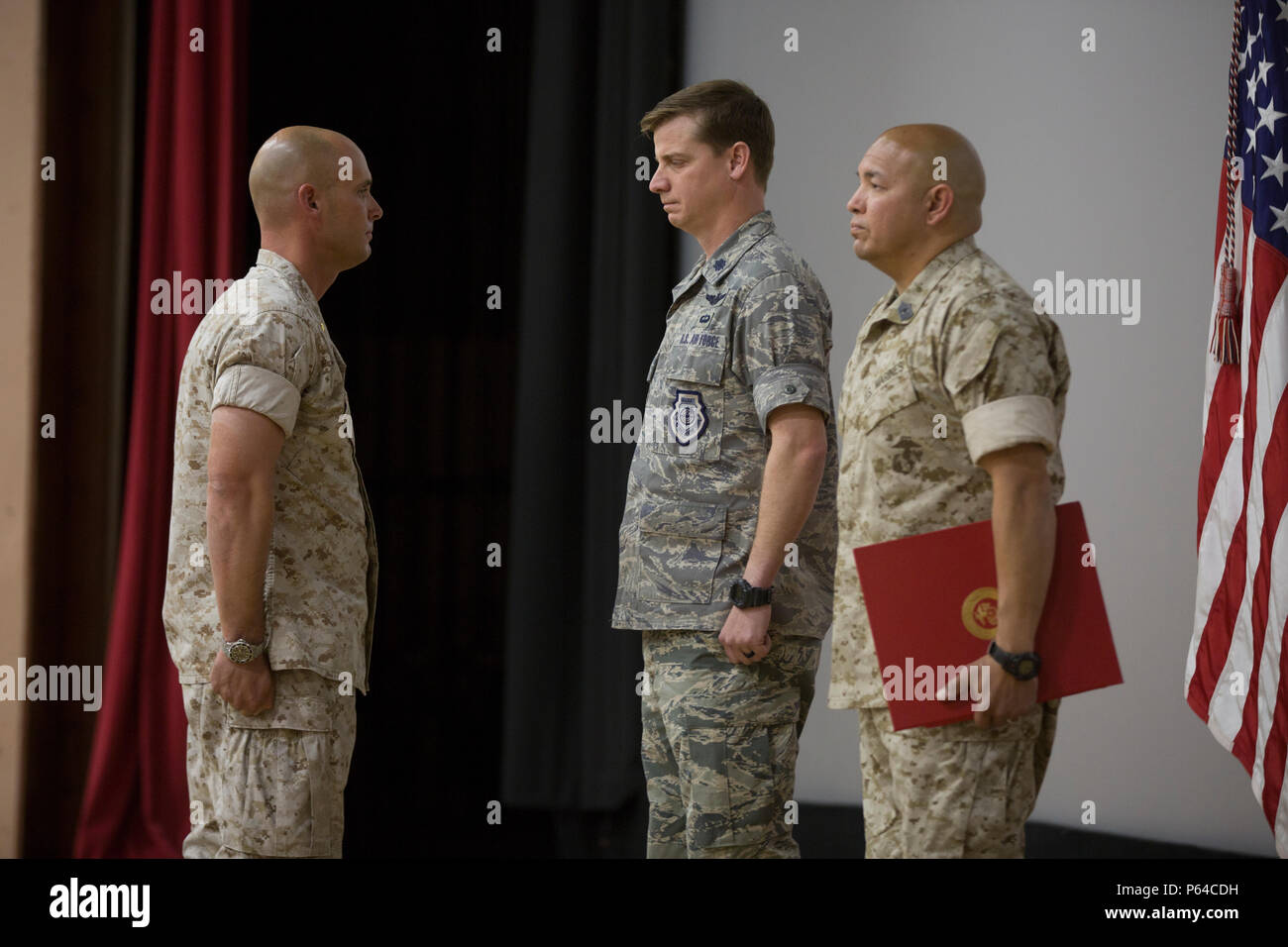 "U.S. Marine Corps Maj. Chad E. Craven, commanding officer, Delta Company, Communication Training Battalion, U.S. Air Force Lt. Col.  Russell ""Bones"" Cook, squadron commander, 563 Operations Support Squadron, and Master Gunnery Sgt. Jerry Romero, senior enlisted advisor, Company D, CTB, stand at the position of attention for the reading of Craven's letter of appreciation from President Barack Obama  during Craven's retirement ceremony at the base theater April 20, 2016. Craven retired after 24-years of honorable service. (Official Marine Corps photo by Cpl. Julio McGraw/Released) - Stock Image"