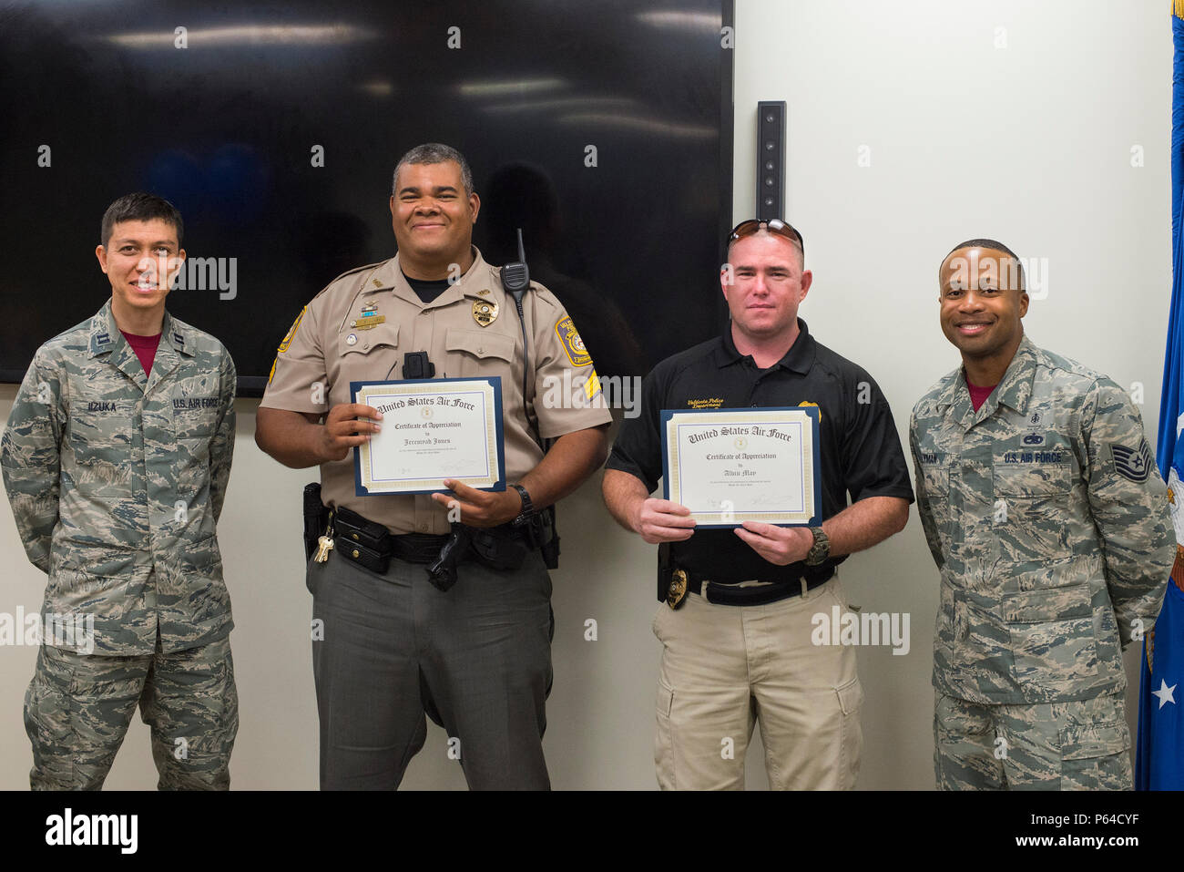 U.S. Air Force Capt. Koji Iizuka, left, and Tech. Sgt. Ronnie Lyman, right, 23d Medical Operations Squadron, present Valdosta Police Department Sgt. Jeremyah Jones, center left, and patrolman Alvin May, with a certificate of appreciation at a lunch and learn, April 8, 2016, at Moody Air Force Base, Ga. The officers received the certificates after speaking to Airmen about the dangers irresponsible drinking in observation of Alcohol Awareness Month. (U.S. Air Force photo by Airman Daniel Snider/Released) - Stock Image