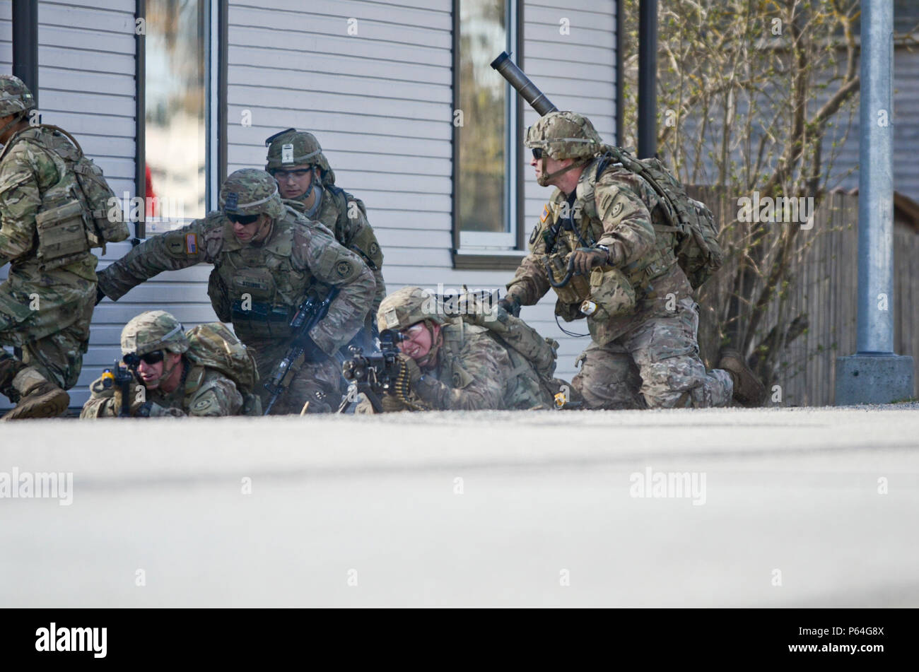 U.S. Soldiers of Eagle Troop, 2nd Squadron, 2nd Cavalry Regiment, stationed out of Vilseck, Germany, suppress enemy fire during an urban operations exercise in Voru, Estonia, April 30, 2016. (Photo by U.S. Army Staff Sgt. Steven M. Colvin/Released) - Stock Image