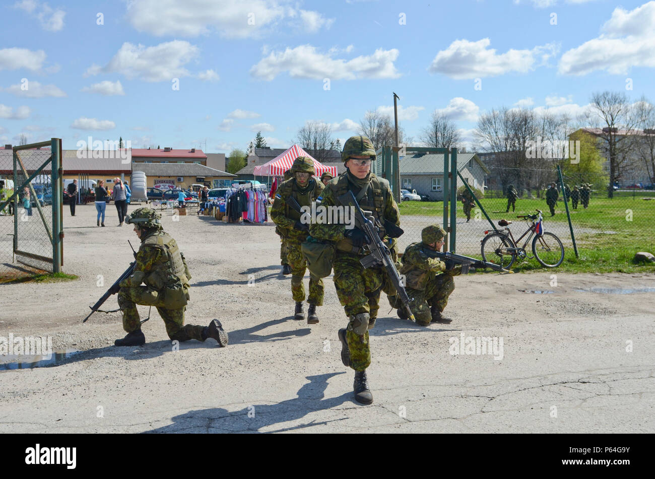 Estonian Soldiers of 2nd Infantry Brigade, Kuperjanov Battalion, move through an open market in the center of town during an urban operations exercise, Voru, Estonia, April 30,2016. (Photo by U.S. Army Staff Sgt. Steven M. Colvin/Released) - Stock Image