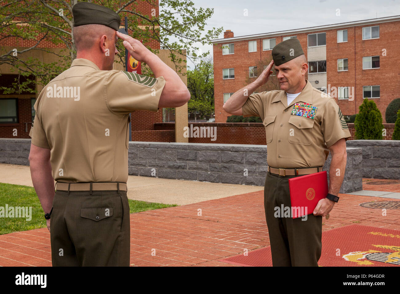 U.S. Marine Corps Sergeant Maj. Robert B. Pullen, battalion sergeant major of Headquarters and Services (H&S) Battalion, Joint Base Myer-Henderson Hall, right, salutes with 1st Sgt. Keith Connor, H&S Battalion 1st Sergeant, at Henderson Hall, April 22, 2016. Marines gathered on behalf of Col. Andrew M. Regan, commanding officer of H&S Battalion, receiving the Defense Superior Service Medal for his actions during Operation Enduring Freedom and Operation Freedom's Sentinel. (U.S. Marine Corps photo by Lance Cpl. Hailey D. Stuart/Released) - Stock Image
