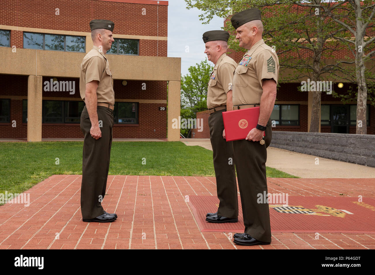 U.S. Marine Corps Capt. Jeffrey J. Rollins, left, supply officer for Headquarters and Services (H&S) Battalion, Joint Base Myer-Henderson Hall, stands at the position of attention with Col. Andrew M. Regan, middle, commanding officer, H&S Battalion, and Sergeant Maj. Robert B. Pullen, battalion sergeant major of H&S Battalion, during his award ceremony at Henderson Hall, Arlington, Va., April 22, 2016. Rollins was awarded the Navy and Marine Corps Commendation Medal, and Regan was awarded the Defense Superior Service Medal. (U.S. Marine Corps photo by Lance Cpl. Hailey D. Stuart/Released) - Stock Image