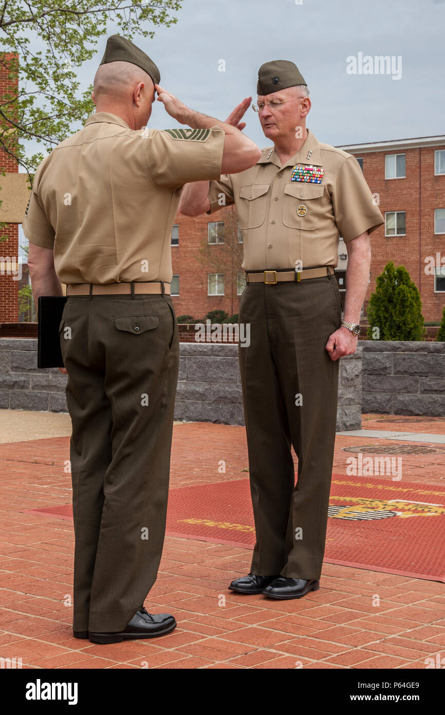 U.S. Marine Corps Lt. Gen. James B. Laster, director, Marine Corps Staff, right, salutes with Sgt. Maj. Robert B. Pullen, battalion sergeant major of Headquarters and Services Battalion, Joint Base Myer-Henderson Hall, during Regan's award ceremony in Arlington, Va., April 22, 2016. Regan was awarded the Defense Superior Service Medal for his actions during Operation Enduring Freedom and Operation Freedom's Sentinel. (U.S. Marine Corps photo by Lance Cpl. Hailey D. Stuart/Released) - Stock Image