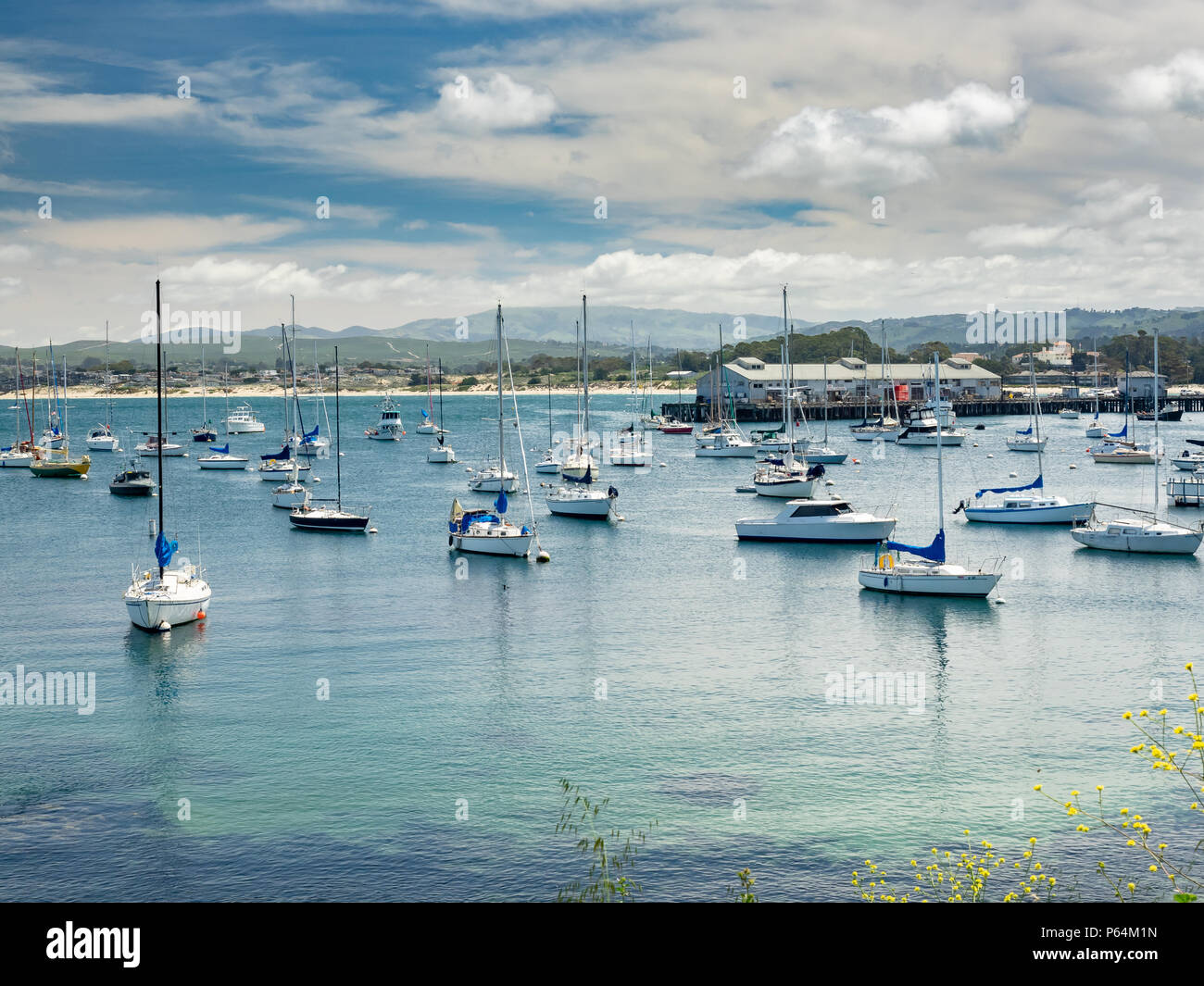 Boats anchored on Monterey Bay in front of the Municipal Wharf II, Monterey, California, USA. - Stock Image