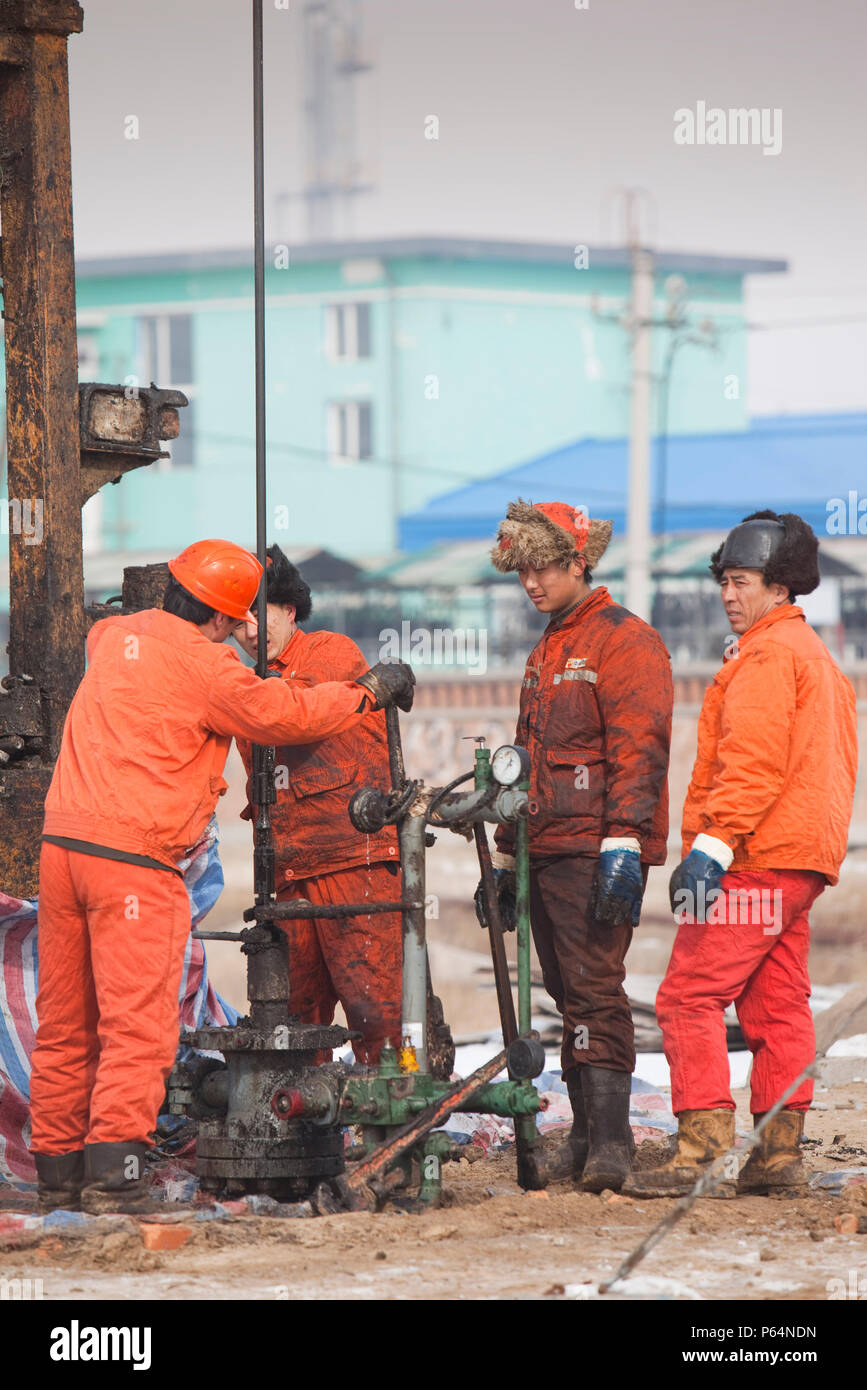 Oil workers drilling a new oil well in the Daqing oil field in Northern China - Stock Image