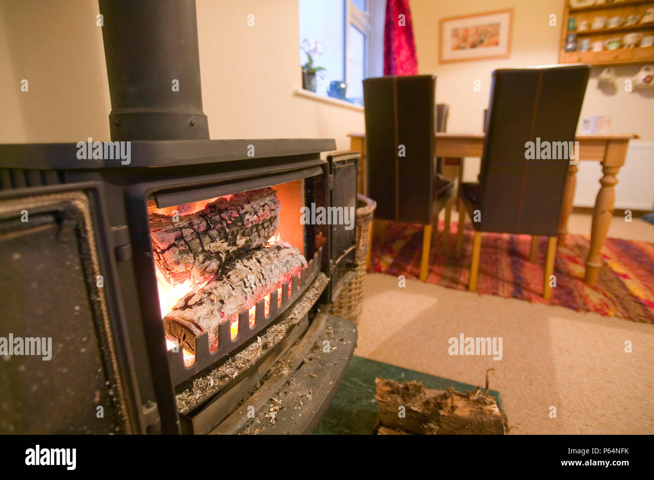 Using a log burning stove to heat a house is burning renewable fuel and therefore C02 neutral. Good for the carbon footprint - Stock Image
