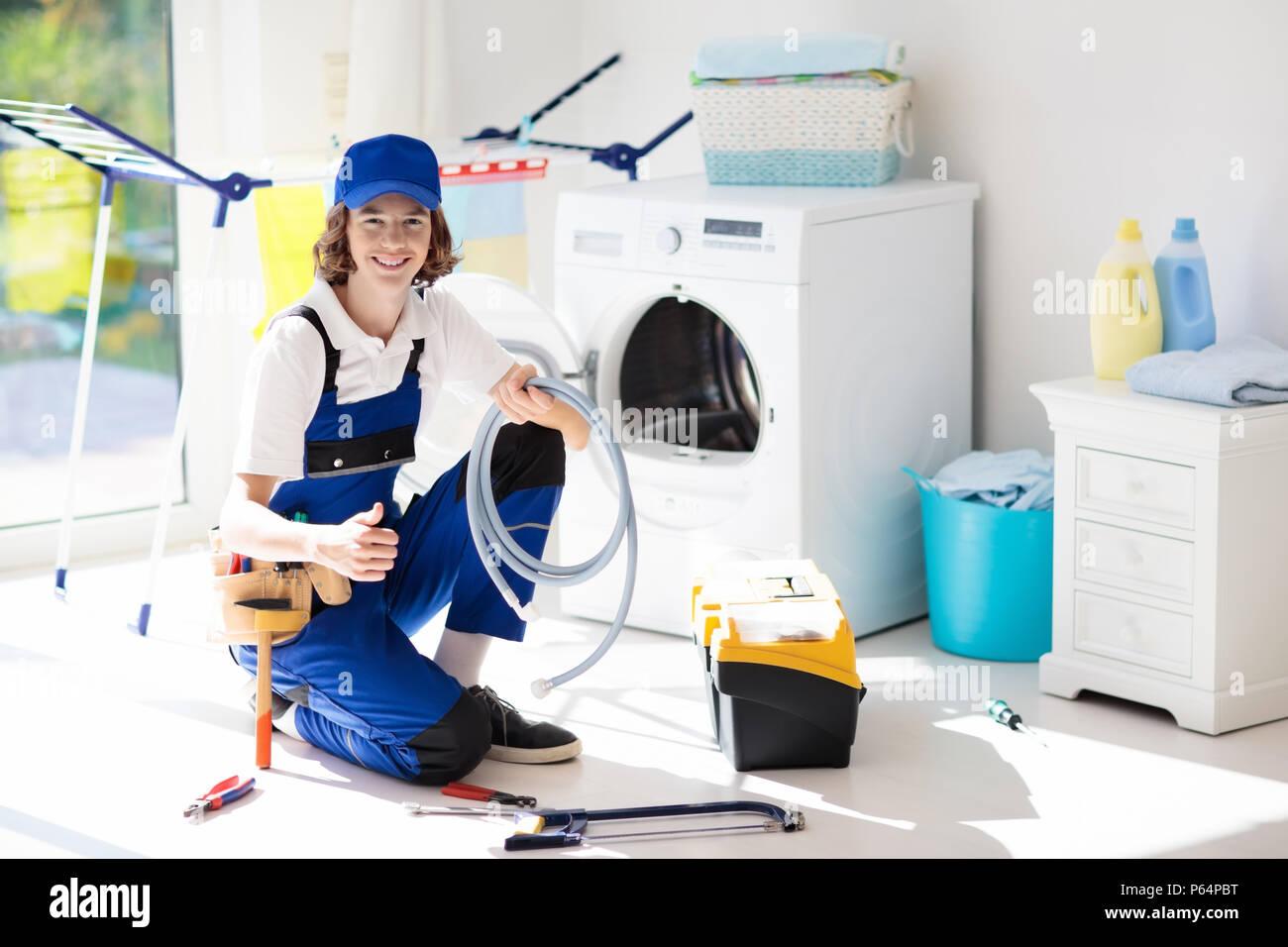 Washing machine repair service  Young male technician in blue