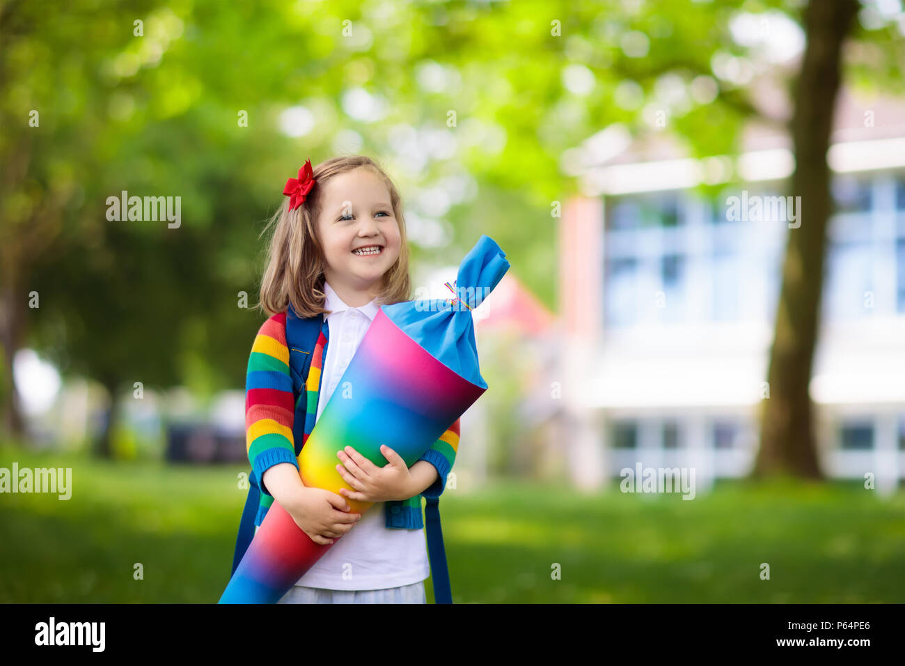 Happy child holding traditional German candy cone on the first school day. Little student with backpack and books excited to be back to school. Beginn Stock Photo
