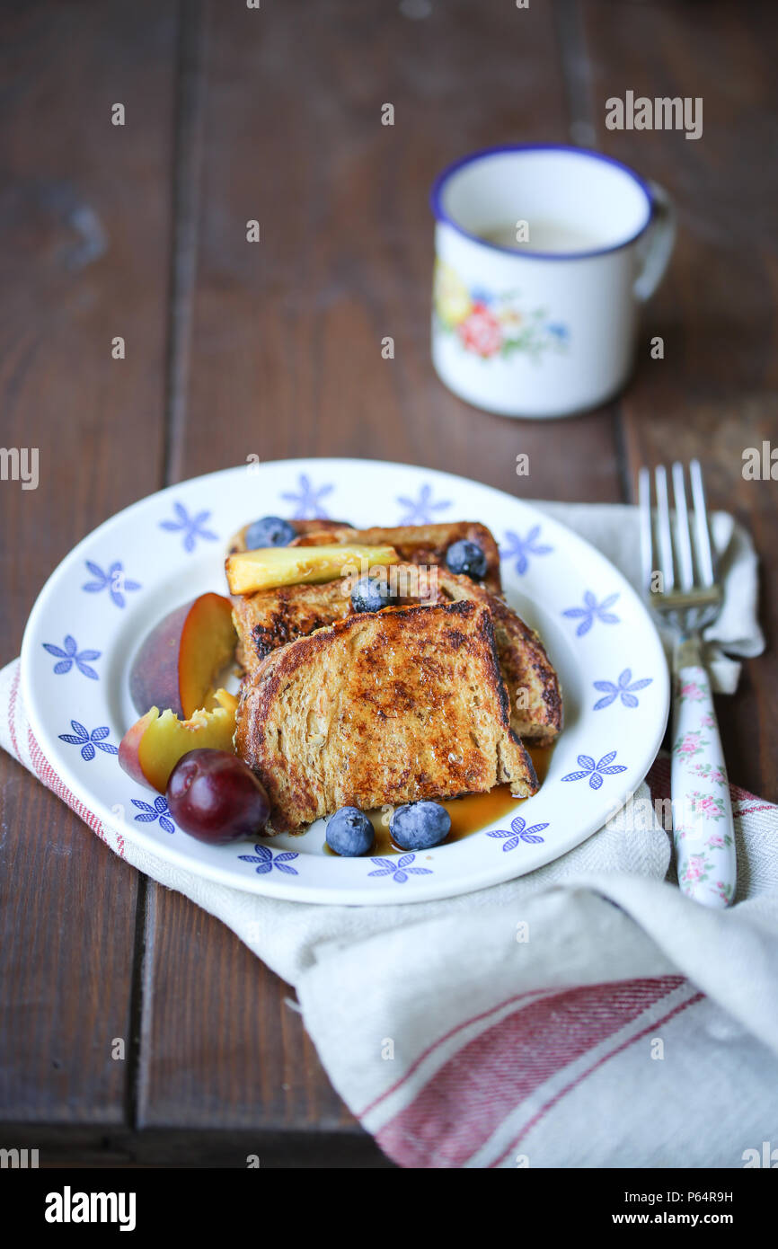 French toast and fruits in a white plate - Stock Image