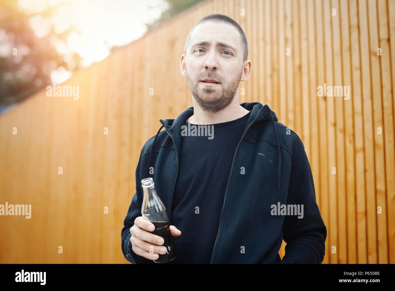 Bearded man holding cola bottle. - Stock Image