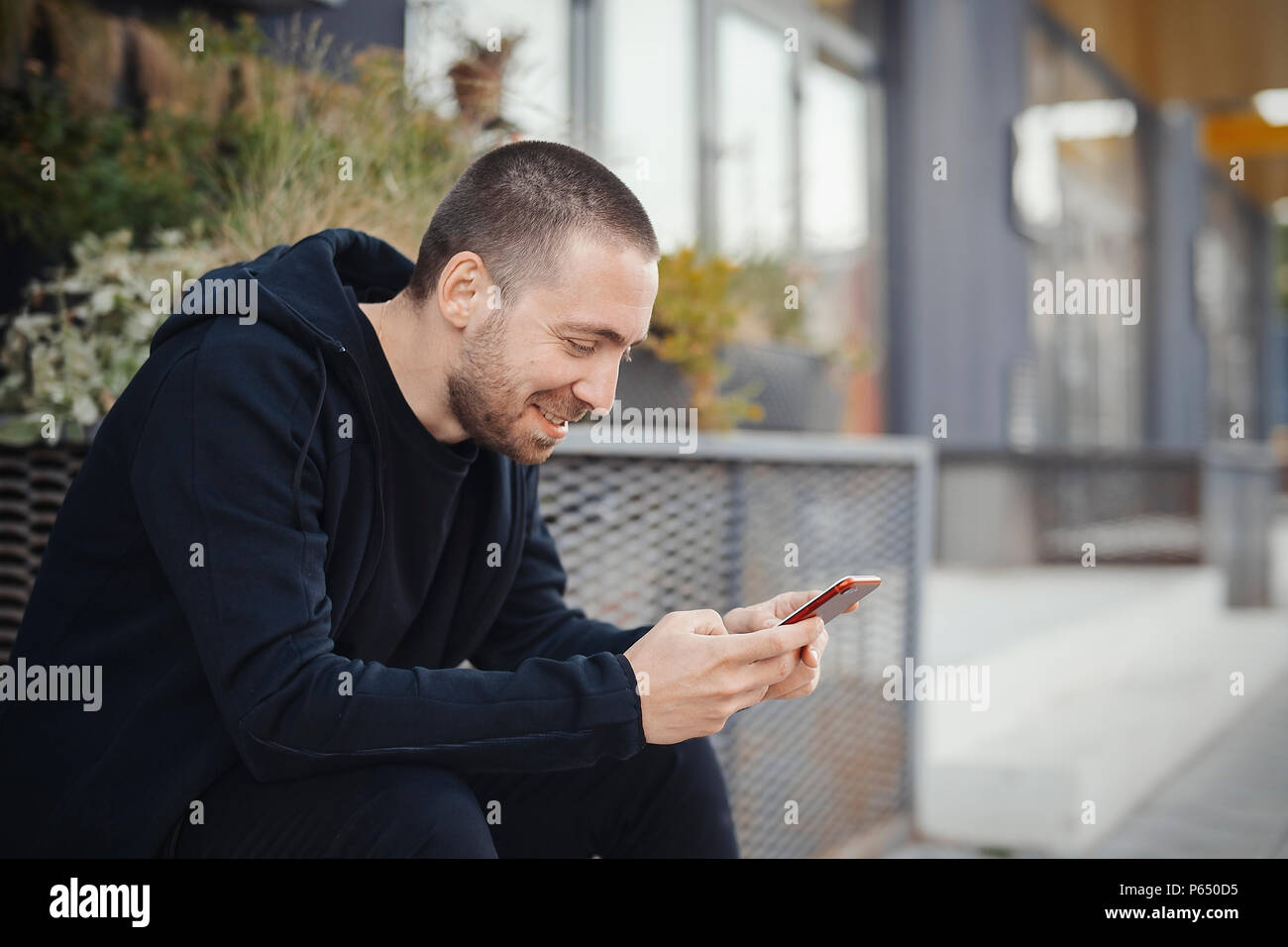 Bearded man looking at mobile phone screen and smiling. - Stock Image